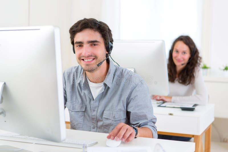Junger attraktiver Mann, der in einem Call-Center arbeitet lizenzfreie stockbilder