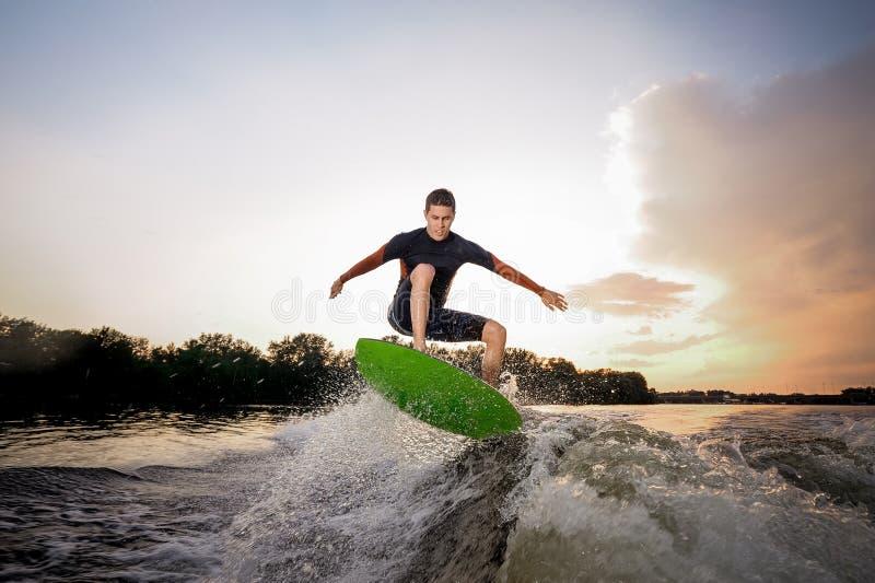 Junger attraktiver Mann, der einen Sprung auf dem grünen wakeboard macht lizenzfreie stockbilder