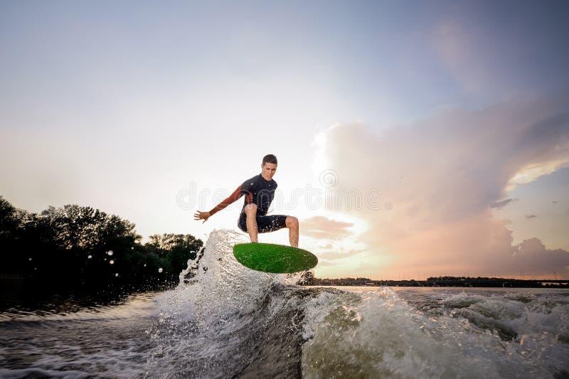 Junger attraktiver Mann, der einen Sprung auf dem wakeboard macht stockfoto