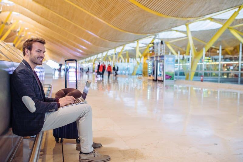 Junger attraktiver Mann, der am Flughafen arbeitet mit einem lapto sitzt stockfotos