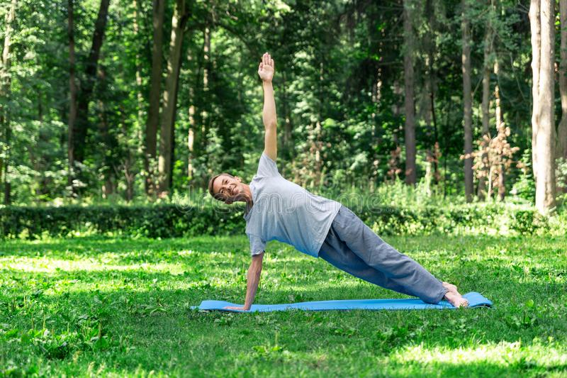 Junger attraktiver Mann, der Yoga im Park tut: Lageplanke lizenzfreies stockfoto