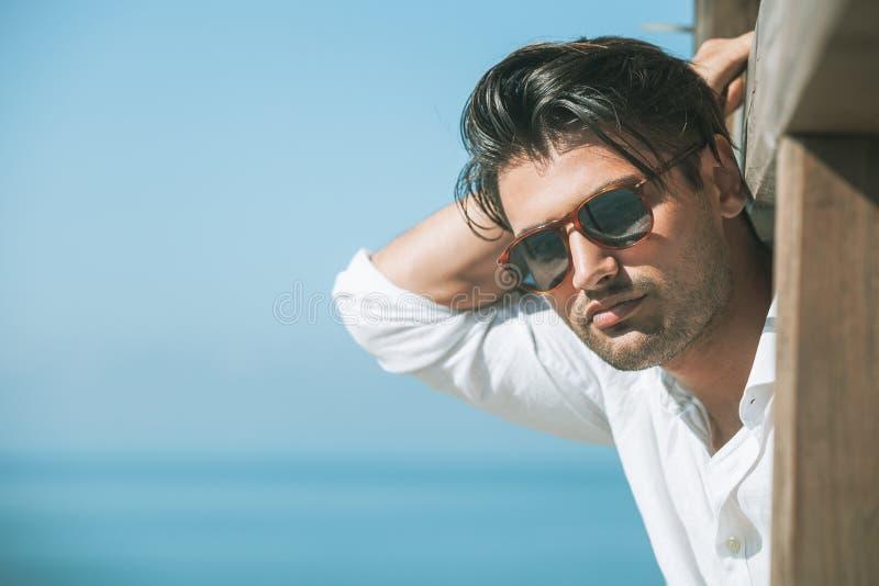 Junger attraktiver Mann mit der Sonnenbrille, die heraus über dem Meer während des Sommers schaut lizenzfreies stockbild