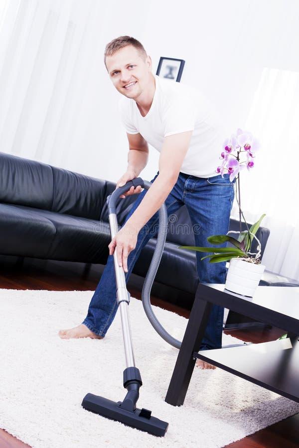 Junger attraktiver Mann säubert Vakuum auf Teppich. stockfoto