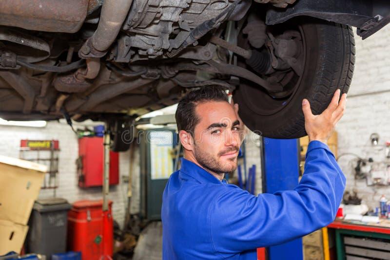 Junger attraktiver Mechaniker, der an einem Auto an der Garage arbeitet lizenzfreie stockfotos