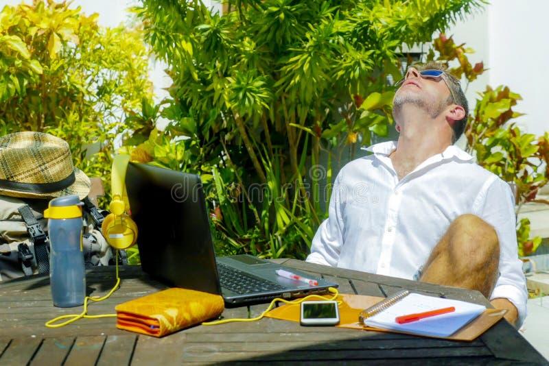 Junger attraktiver und glücklicher digitaler Nomademann, der draußen von der Kaffeestube mit der Laptop-Computer sich lehnen zurü stockbild