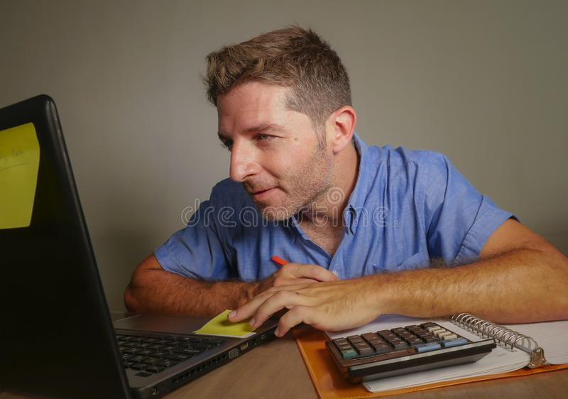 Junger attraktiver und glücklicher Geschäftsmann, der zu Hause mit Laptop-Computer dem Bürolächeln zufrieden gestellt und überzeu stockbild