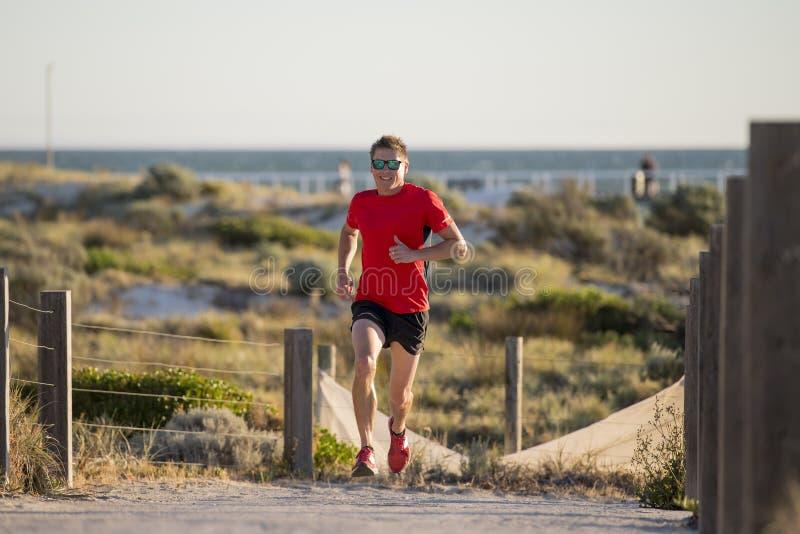 Junger attraktiver und glücklicher Sportläufermann mit Sitz und starkem gesundem Körpertraining auf weg von Straßenbahn in laufen stockfoto