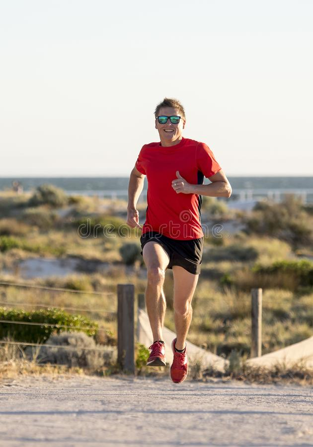 Junger attraktiver und glücklicher Sportläufermann mit Sitz und starkem gesundem Körpertraining auf weg von Straßenbahn in laufen stockfotografie