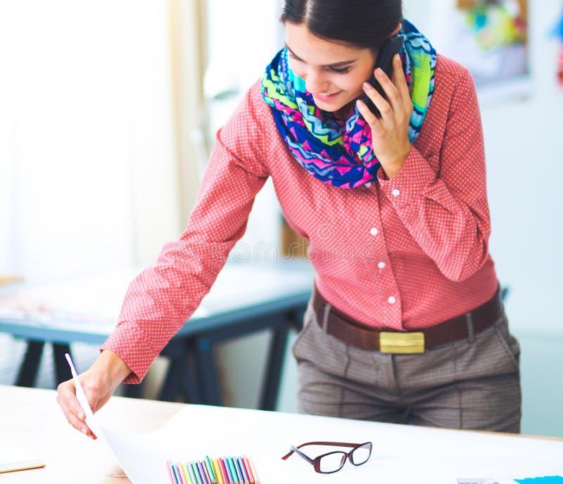 Junger attraktiver weiblicher Modedesigner, der am Büroschreibtisch, zeichnend bei der Unterhaltung auf Mobile arbeitet lizenzfreie stockfotografie