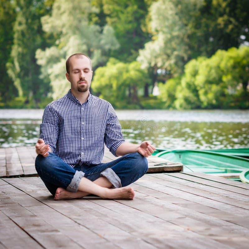 Junger auf hölzernem Pier sitzender und meditierender Mann stockfoto