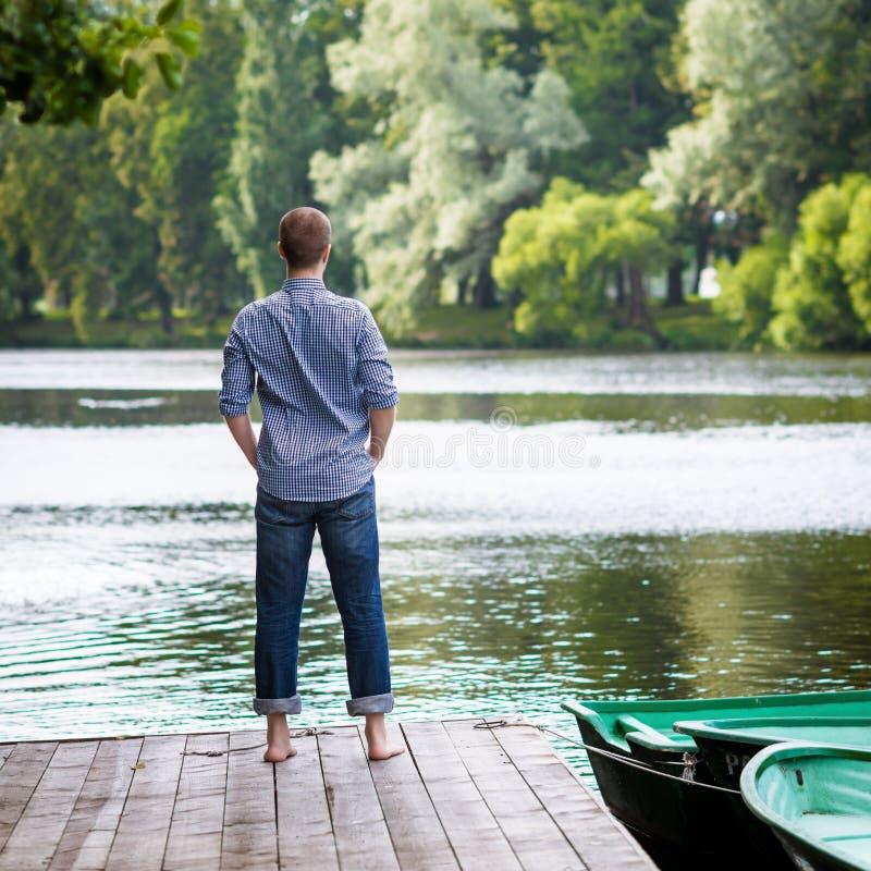 Junger auf hölzernem Pier stehender, entspannender und meditierender Mann lizenzfreie stockbilder