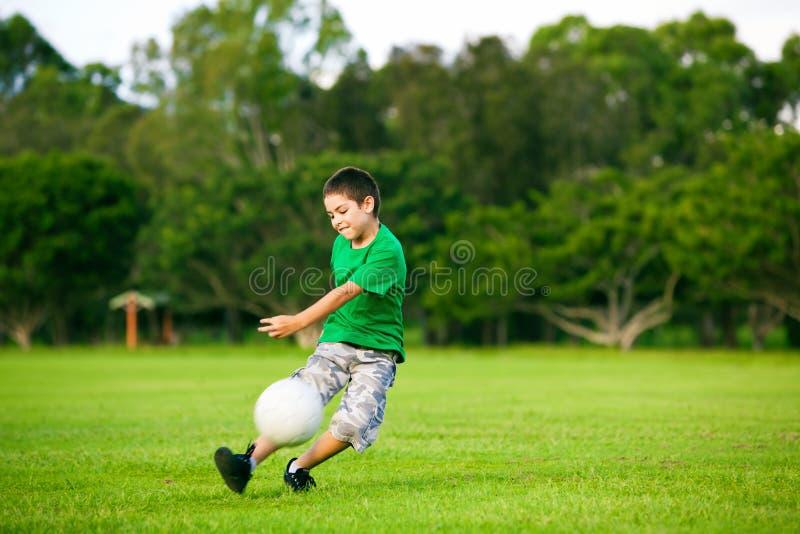 Junger aufgeregter Junge, der Kugel im Gras tritt lizenzfreie stockbilder