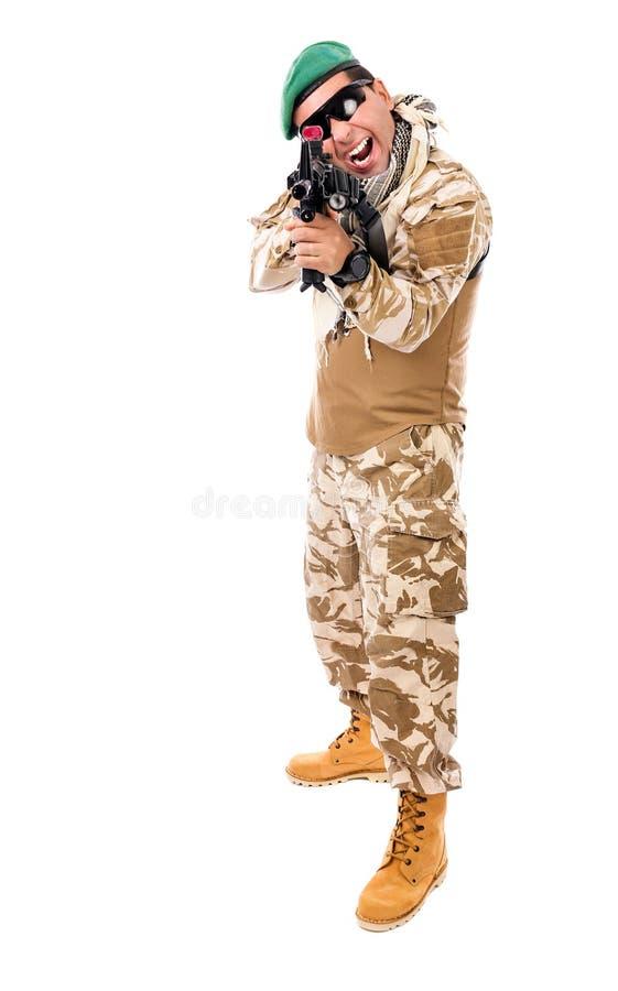 Junger aufgeregter Soldat in der Armeekleidung und Tarnung, die mit zielt stockfotografie