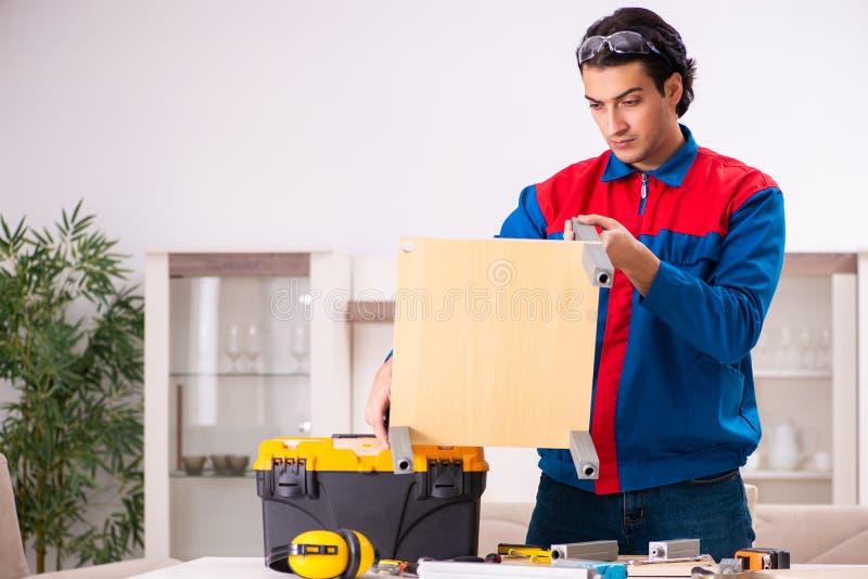 Junger Auftragnehmer, der zu Hause M?bel repariert lizenzfreies stockfoto