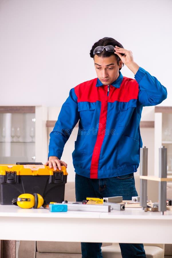 Junger Auftragnehmer, der zu Hause M?bel repariert lizenzfreie stockfotos