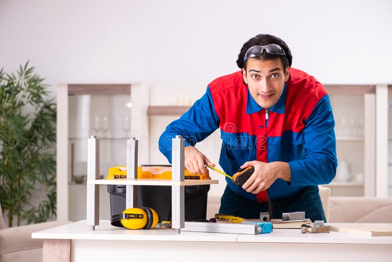Junger Auftragnehmer, der zu Hause M?bel repariert stockbilder