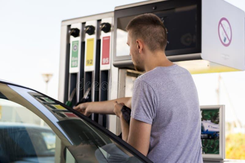 Junger Autofahrermann in zufälligem auf Brennstoffstation nahe Gaspumpe lizenzfreie stockfotografie