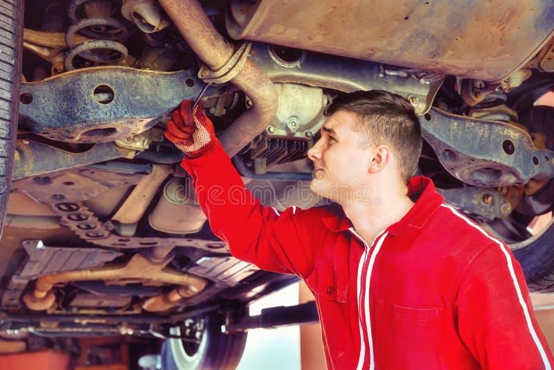 Junger Automechaniker in der Uniform, die unter ein angehobenes Auto w arbeitet stockfotografie