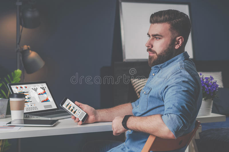 Junger bärtiger Geschäftsmann im Denimhemd sitzt zu Hause bei Tisch und hält Handy mit Diagrammen, Diagramme stockbild