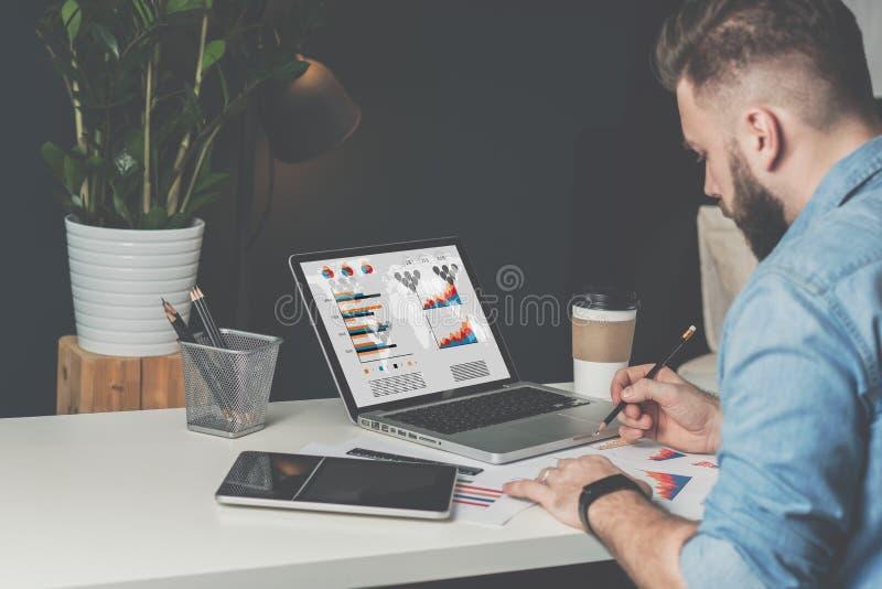 Junger bärtiger Geschäftsmann sitzt im Büro bei Tisch und erforscht die Diagramme und macht Anmerkungen lizenzfreies stockbild