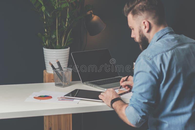 Junger bärtiger Geschäftsmann sitzt im Büro bei Tisch, unter Verwendung der digitalen Tablette und erforscht die Diagramme und ma lizenzfreie stockbilder