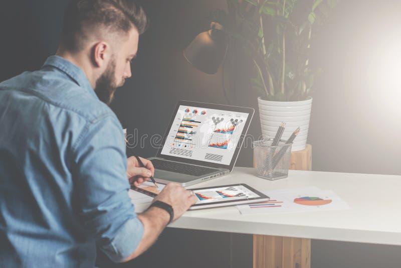 Junger bärtiger Geschäftsmann sitzt im Büro bei Tisch, unter Verwendung des Tablet-Computers und erforscht die Diagramme und mach lizenzfreies stockfoto