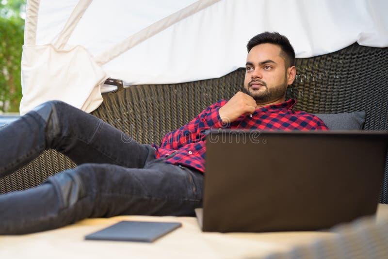 Junger bärtiger indischer Geschäftsmann, der sich im Einkaufszentrum in Bangkok entspannt stockbilder