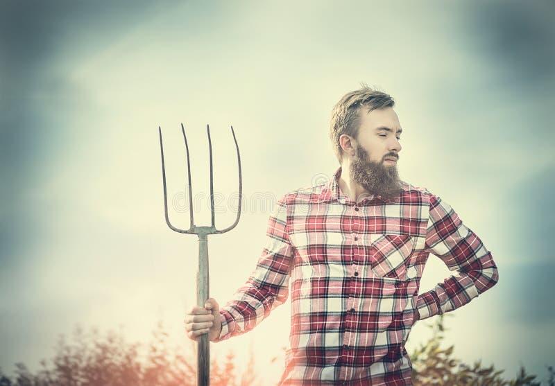 Junger bärtiger Landwirt im roten karierten Hemd mit altem Heugabelhimmel-Natur backgrund, getont stockfotografie