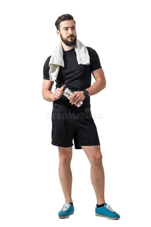 Junger bärtiger männlicher Athlet mit dem Tuch, das Plastikwasserflasche hält stockfotografie