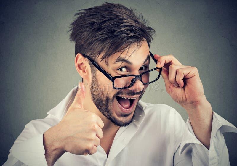 Junger bärtiger Mann in den Gläsern, die sich Daumen zeigen lizenzfreies stockfoto