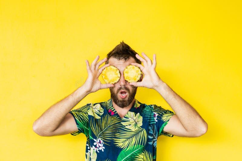 Junger bärtiger Mann, der die Scheiben von Ananas vor seinen Augen, überrascht hält stockbild