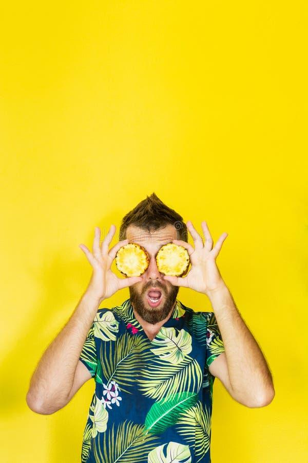 Junger bärtiger Mann, der die Scheiben von Ananas vor seinen Augen, überrascht hält lizenzfreie stockbilder