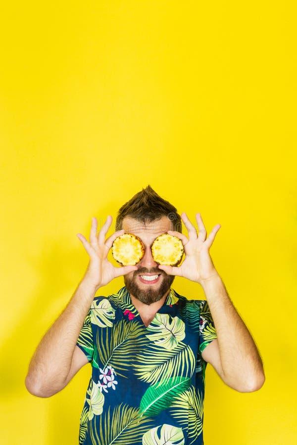Junger bärtiger Mann, der die Scheiben von Ananas vor seinen Augen, lachend hält lizenzfreie stockfotos
