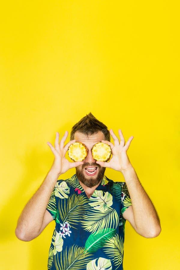 Junger bärtiger Mann, der die Scheiben von Ananas vor seinen Augen, lautes heraus lachend hält stockfotos