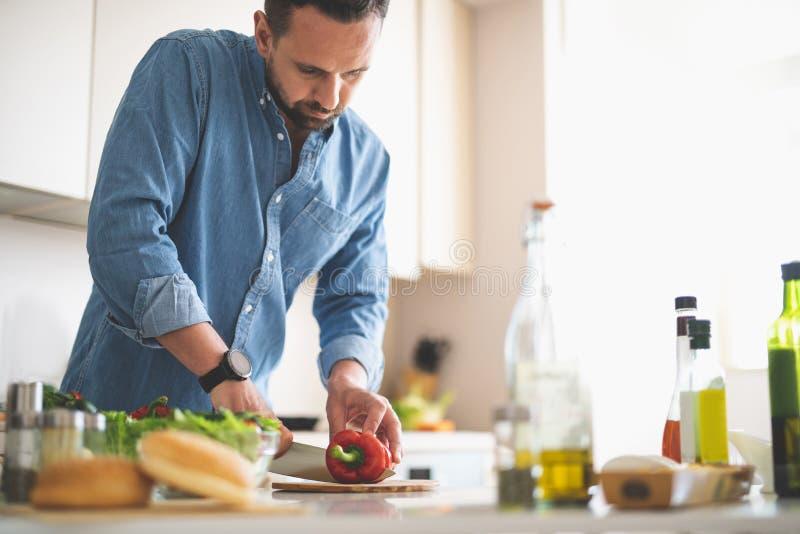 Junger bärtiger Mann, der Gemüse für Abendessen vorbereitet stockfotografie