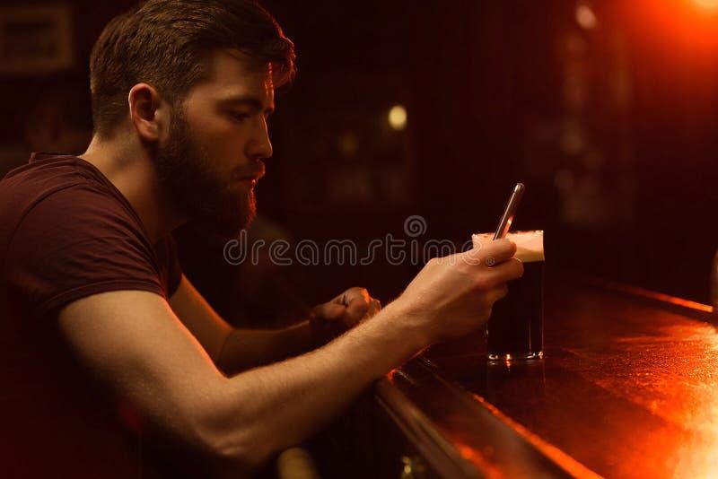 Junger bärtiger Mann, der Handy beim Essen des Bieres verwendet lizenzfreies stockbild