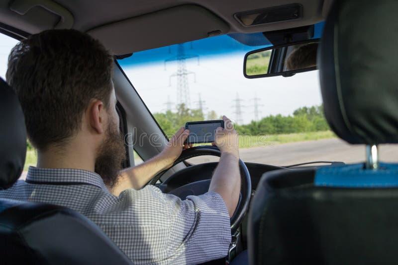 Junger bärtiger Mann, der hinter dem Rad sitzt und nach Weg durch Navigationskarte im Smartphone sucht Hintere Ansicht stockbild
