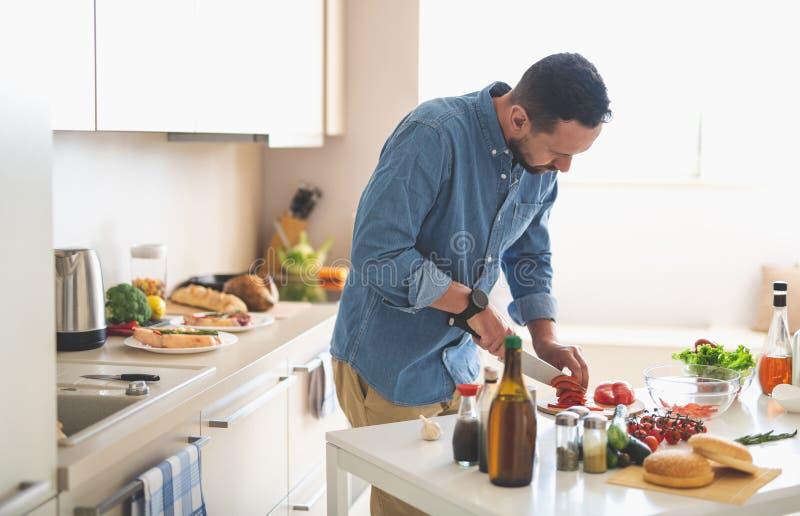 Junger bärtiger Mann, der roten grünen Pfeffer mit Messer schneidet lizenzfreies stockbild