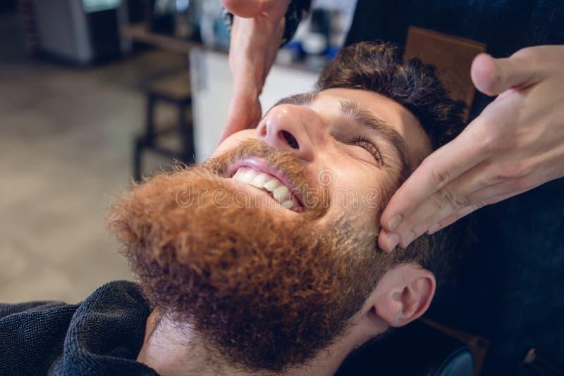 Junger bärtiger Mann, der während einer entspannenden Tempelmassage lächelt lizenzfreies stockfoto