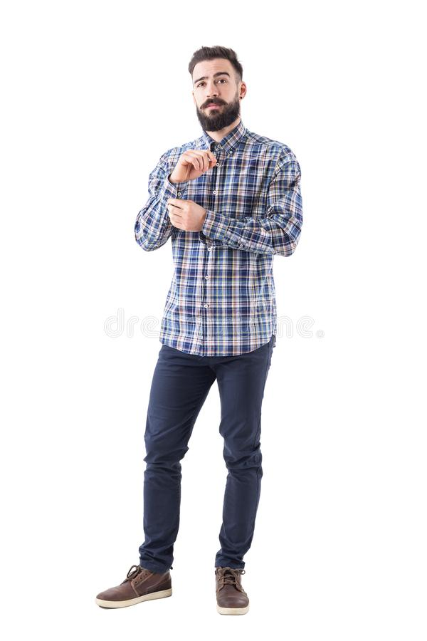Junger bärtiger Mann erhalten angekleidet, Ärmelknöpfe knöpfend und Kamera sicher betrachtend lizenzfreies stockfoto