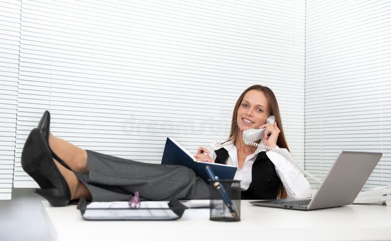 Junger Büroangestellter, der am Telefon spricht stockbild
