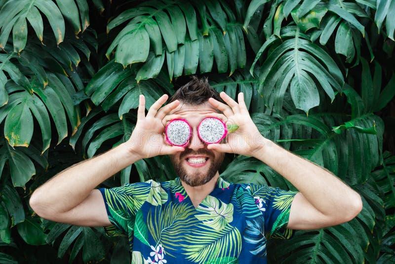 Junger b?rtiger Mann, der die Scheiben der Pitaya-Drachefrucht vor seinen Augen, lachend h?lt lizenzfreie stockbilder