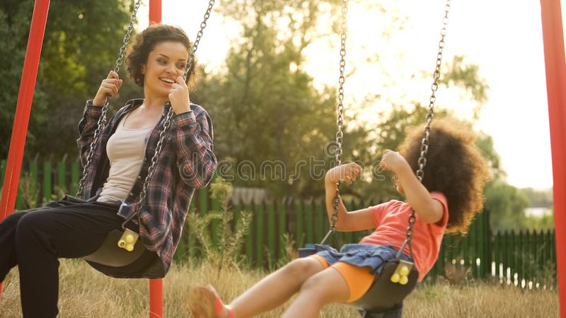 Junger Babysitter, der mit sorglosem Kind, Schwingen im Freien am Kinderspielplatz spielt stockbilder