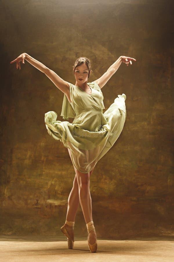 Junger Balletttänzer - harmonische hübsche Frau mit dem Ballettröckchen, das im Studio aufwirft - lizenzfreies stockfoto