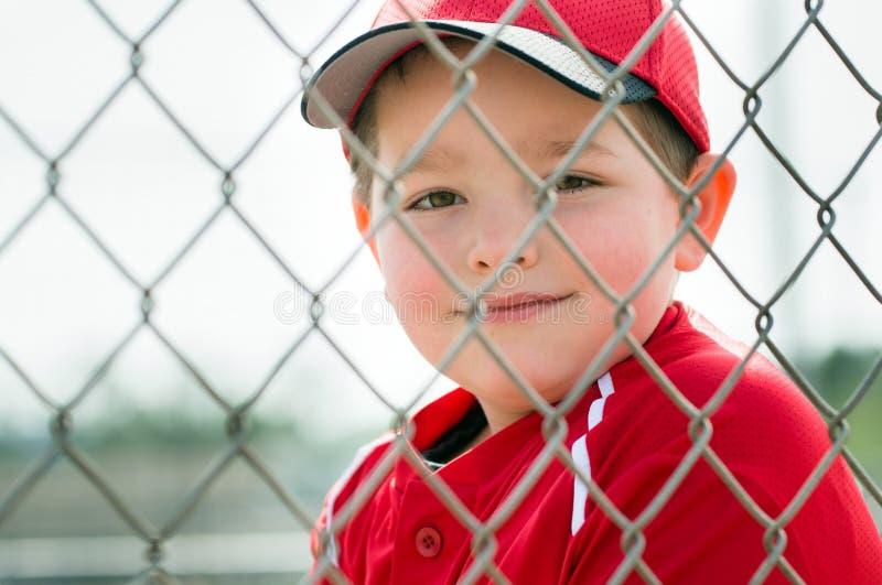 Junger Baseball-Spieler, der im Einbaum sitzt lizenzfreie stockfotos