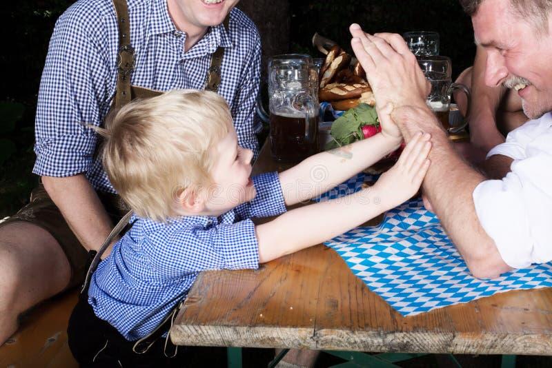 Junger bayerischer Junge mit Vater an beergarden lizenzfreie stockbilder