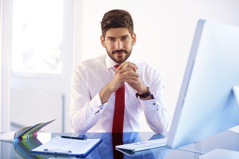 Junger behilflicher finanziellgeschäftsmann, der an Computer arbeitet lizenzfreie stockfotos