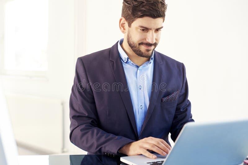 Junger behilflicher finanziellgeschäftsmann mit Notizbuch im Büro lizenzfreie stockfotografie
