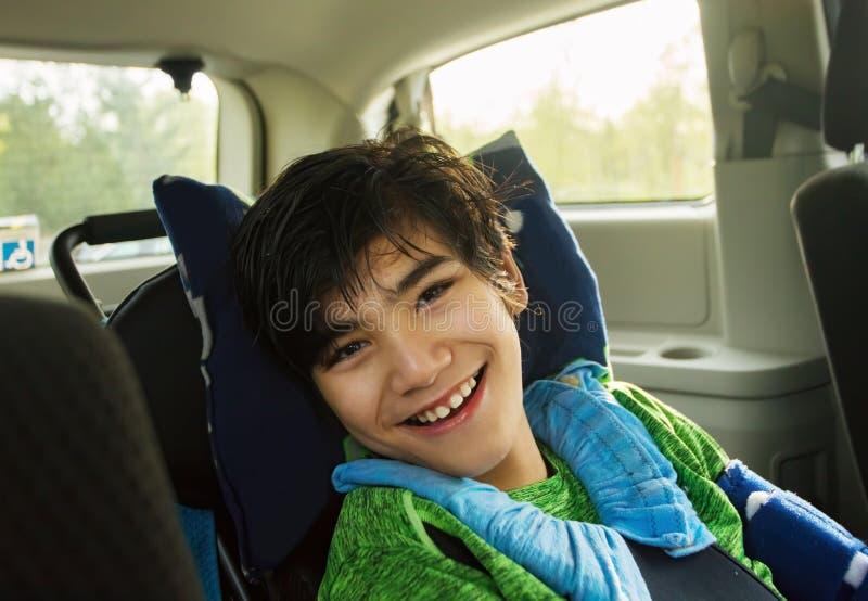 Junger behinderter Junge im Rollstuhl, der in Handikapfahrzeug reist stockfotos