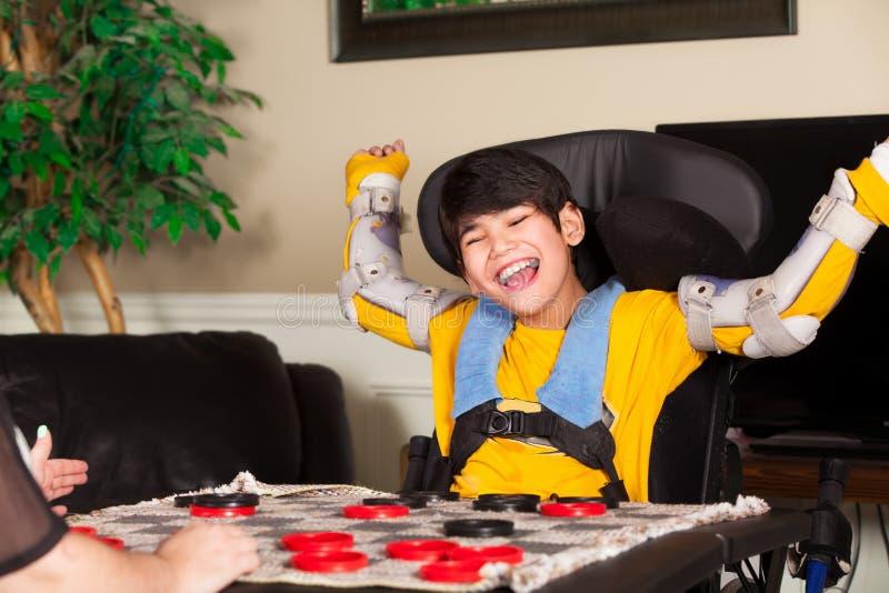 Junger behinderter Junge im Rollstuhl, der Kontrolleure spielt lizenzfreie stockbilder